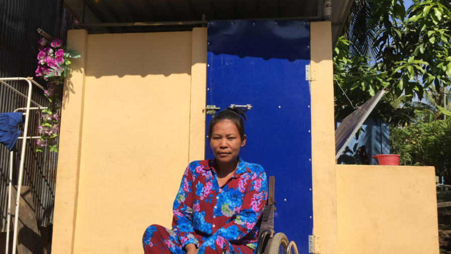 A female wheelchair user outside her house