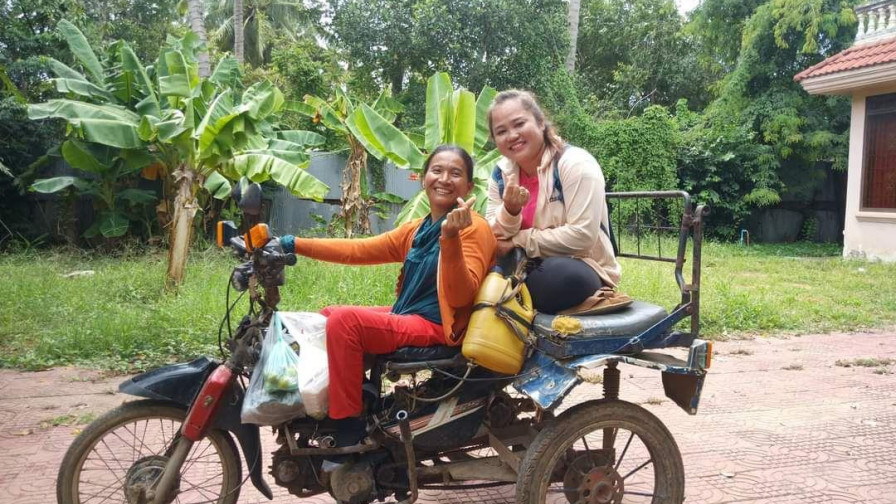 Two women on a motorbike smiling at camera