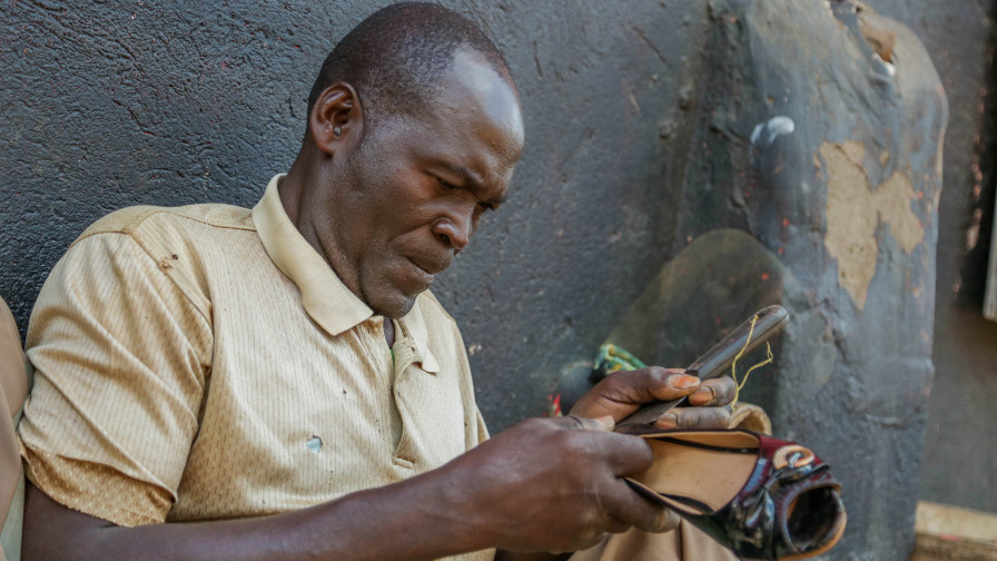 Stephen concentrates as he fixes a shoe in his workshop