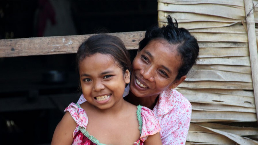 a mother and daughter smiling