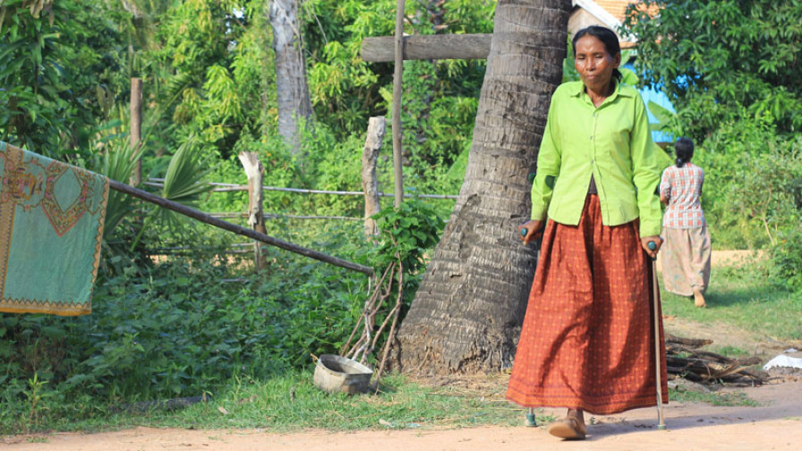 A woman with a physical impairment walking in her village