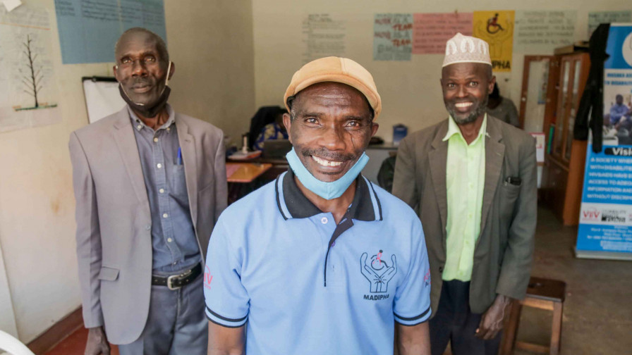 Three male activists standing smiling to camera