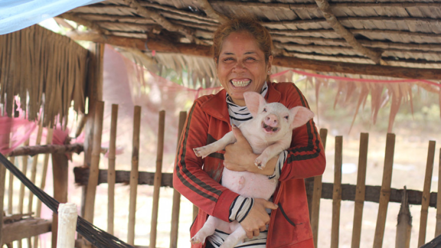 a woman holding her pig smiling