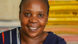 A photograph of Christine smiling at the camera, she is sat in her shop in Uganda