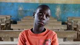 Eric, a visually impaired boy from Tanzania, sat in an empty classroom.