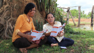 Two women reading about disability rights in a village
