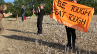 Tough mudder, woman holding banner reading 'Be tough, beat tough'