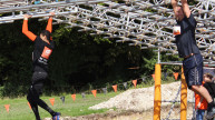 Tough mudder, boy climbing monkey bars over cold water