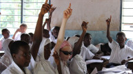 Children raising their hands in a Tanzanian classroom