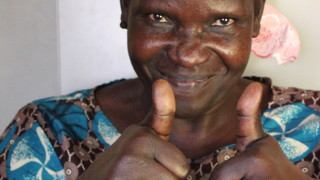 A disability activist in Uganda smiling and giving a thumbs up to camera