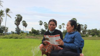 Two Cambodian women reading an ADD leaflet