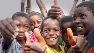 a group of smiling children giving a thumbs up