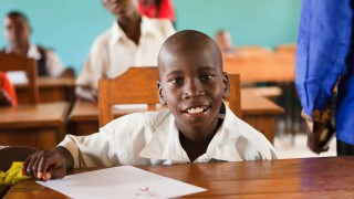 A boy in a classroom in Tanzania smiling to camera