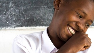 A Tanzanian student smiling in from of the blackboard
