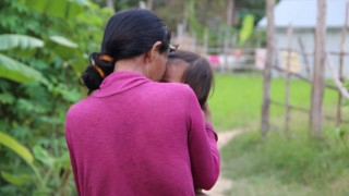 A disabled woman turned away from camera carrying her child, Cambodia