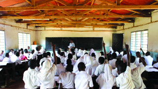 Students in a classroom, hands raised