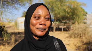 A visually impaired woman smiling into the camera in Sudan