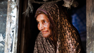 A older woman in Bangladesh smiling outside her house