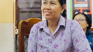 A female disability activist smiling whilst listening at a meeting