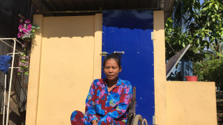A wheelchair user outside her home in Cambodia