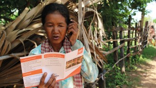 A Cambodian activist reading an ADD Leaflet on the telephone