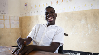 A student smiling in a classroom in Tanzania