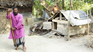 A disability activist in Bangladesh walking along a rural street smiling