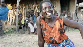 A lady smiling out side her home in rural Uganda