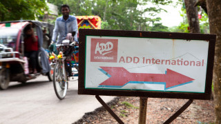 A sign for ADD International on a street in Bangladesh